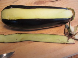 Using a knife remove the leafy part overlapping the flesh by making a shallow cut around the head of the eggplant then peel the skin with a vegetable peeler. Keeping the head will prevent the eggplant from disintegrating while cooking. Also it make s nice presentation.