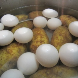 Wash the potatoes, unpeeled and whole, place in a large pan. Add the eggs and fill with cold water covering the top of the eggs. Bring to a boil, reduce heat and simmer for about 20 minutes.