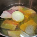 Place the meat, whole onion, salt, pepper, turmeric and water in a large pot.