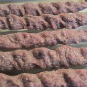 To shape the kabab, take a handful of the meat mixture, wrap around the skewer like a hot dog. Using the palm of your hand, gently press the meat around the skewer forming an evenly long and flat shape.