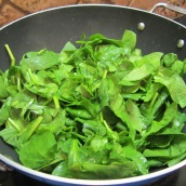 Add spinach to a large nonstick skillet.
