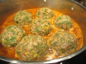 Gently slide the meatballs into the simmering sauce, one at a time.