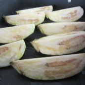 Place eggplants in a non-stick roasting pan. Drizzle with olive oil, coating all sides.