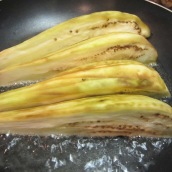 In a large skillet, heat ½ cup oil over medium heat. Add eggplants.