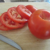 Core and slice the tomatoes.