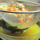 Pour the broth mixture through the strainer. Discard the bones and vegetables.